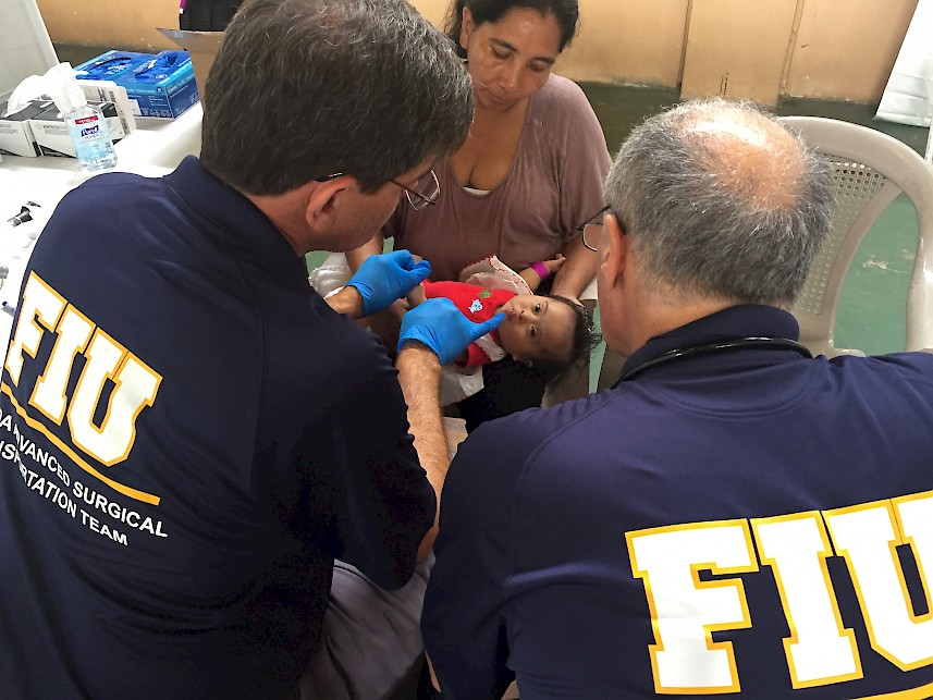 Neonatologist Jaime Fernandez and Emergency Physician Robert Levine assess a Down Syndrome infant in Puerto Barrios, Guatemala (Source: Ruben D. Almaguer, 7 February 2017).