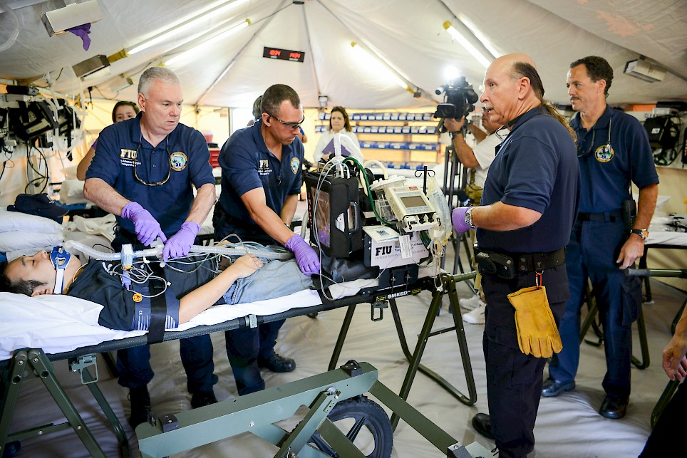 FIU-FAST Team members inside their critical care tent, simulating patient packaging of a critical patient for helicopter transport in Miami, Florida (Source: FIU Media Relations, 29 April 2016).